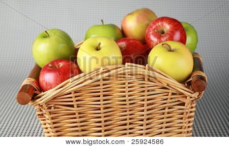 a nice wicker basket filled with hand picked farm fresh red, green and yellow apples on a black and white background