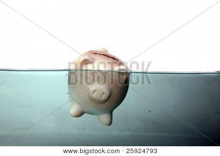 a piggy bank floats in dark murkey water, representing the idea of drowning in debt, or keeping your head above water and other financial concepts