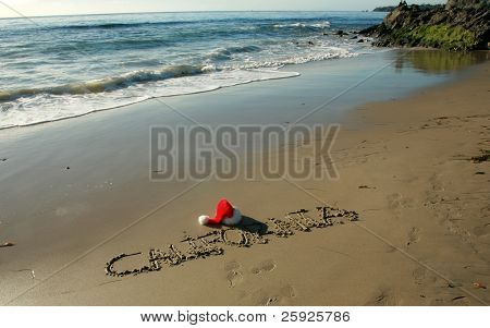 "the word ""California"" written in the wet sand on a southern california beach with a ""Santa Hat""  and a blue sky and nice tide and waves from the pacific ocean"