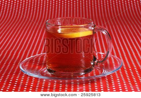 fresh hot tea with a slice of lemon or orange in a clear glass tea cup on a red and white pokadot background