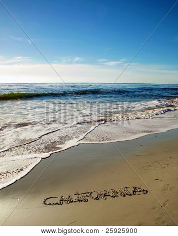 "the word ""California"" written in the wet sand on the world famous Laguna Beach in southern california beach with a blue sky and nice tide and waves from the pacific ocean"