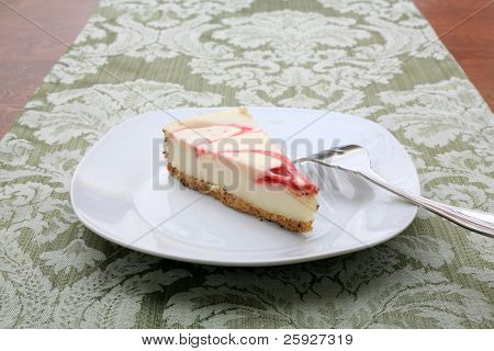 strawberry or raspberry swirl cheesecake on a white plate with a fork on a green table cloth, just waiting for you to eat for your dessert. Enjoy!