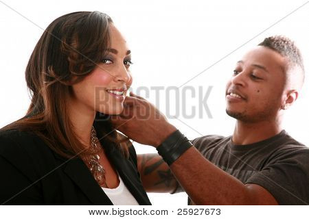 A african american professional cosmetologist brushes a beautiful models hair for a Beauty / Fashion / Hair Style / Makeup photo shoot. Isolated on white with room for your text.
