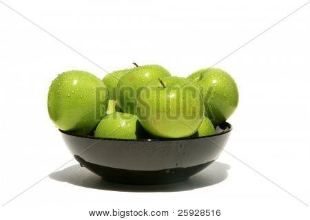fresh picked green granny smith apples in a bowl with water drops isolated on white with room for your text