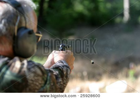 an unidentifiable person shoots a high power pistol. low depth of field photo so the background in out of focus and focus is on the gun and shell casing in the air.
