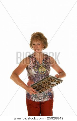 a beautiful woman holds a cookie sheet filled with fresh baked cookies for You the Viewer. Isolated on white with room for your text.