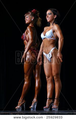 Two girls posing during a junior fitness competition