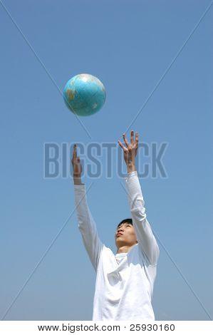Young Asian man playing with a terrestrial globe (globe is in motion)