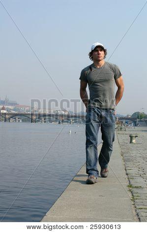 Young sexy man walking along the embankment in Prague, Czech Republic.
