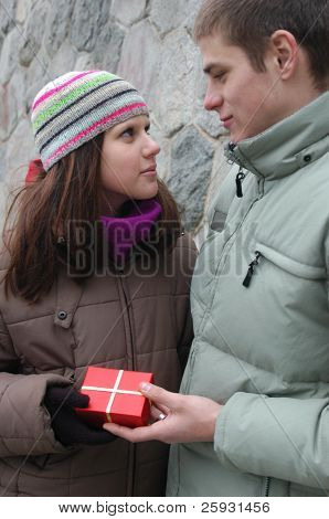 Valentine's Day Gift. Young man giving a red gift box to his girlfriend