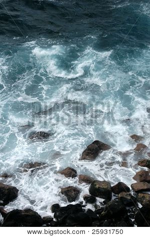 Foamy waves surfing on the rocky seashore