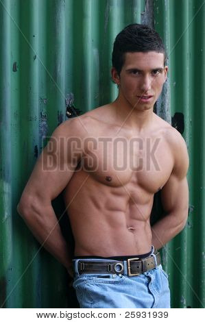 Shirtless muscular male model in front of the green crimping metal wall