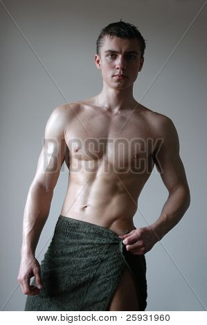 Wat sexy muscular man wrapping a towel after shower