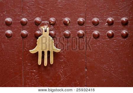 Old knocker in the shape of a hand on a door of a traditional Moroccan house in Marrakech, Morocco.