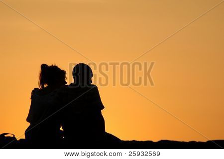 Silhouetted loving couple at sunset