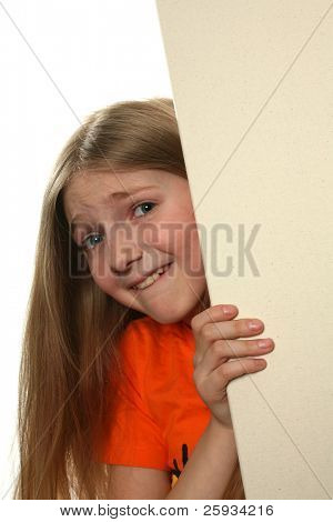 Pretty blond girl peeping over a blank billboard isolated on white