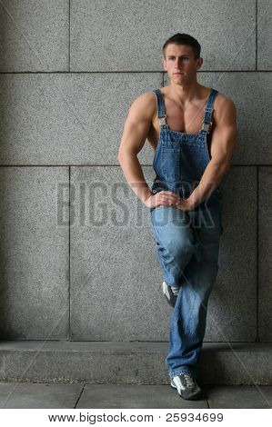 Young sexy muscular worker in a blue coverall leaning on the stonewall