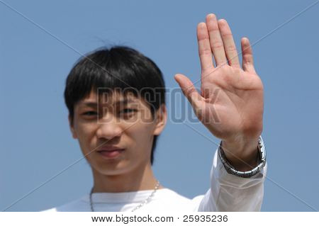 Stop do it now! Young Asian man holding hand up saying 'Stop' or 'No' - palm in focus