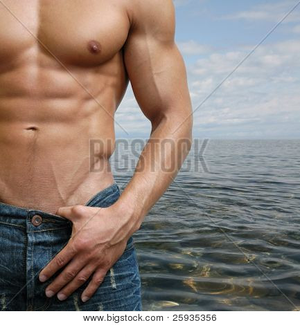 Muscular male torso on the beach