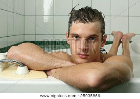 Young muscular man taking bath