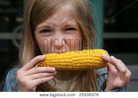 Jovem rapariga comer um milho cozido.