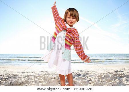 Small cute girl enjoying sunny day at the beach. Shoot against the sun.