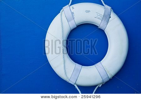 White life buoy hanging on blue wall.