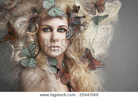 Young beautiful Woman mit Schmetterling in blondes Haar lockig.