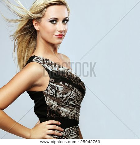 Young attractive happy fashion model witj long hair posing in studio.