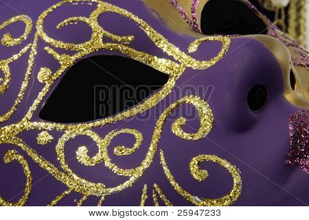 Detail of a beautiful Venetian mask with a half from gold and a half from violet on a black background