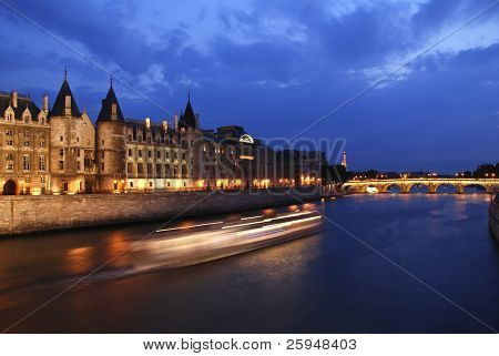 Palais de Justice standing on the banks of river Seine on the island Il de la Cite, Paris - France after the sunset with a boat passing by