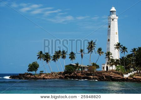 Beautiful white lighthouse Dondra Head, the southest cape of Sri Lanka - seen from the beach. The lighthouse is also a highest (161 feet) not only on the island but also in the whole Asia