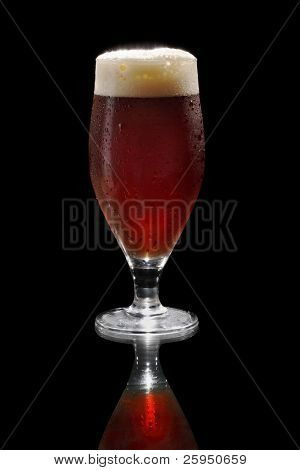 Dark beer in a footed glass on reflective surface.
