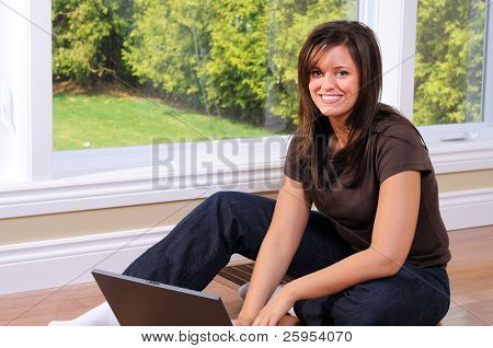 Brunette Young Woman Sat On The Floor Using Her Laptop Computer