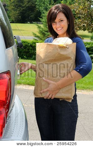 Beautiful Young Mom Loading Groceries Into Her Minivan