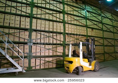 Truck in the warehouse. Boxes on the shelves in the background.