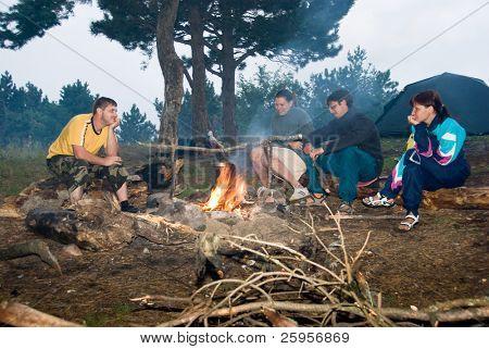 Wanderer sitzen rund um die Lagerfeuer auf dem eine Mahlzeit bereitet