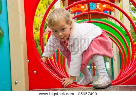 Little girl plays in playground in a park