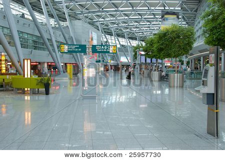 Interior of modern International Airport. No recognizable faces and advertising