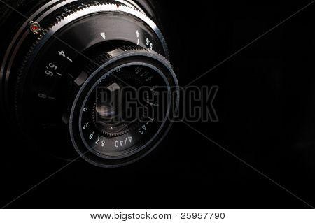 Macro image of lens on retro camera over black background