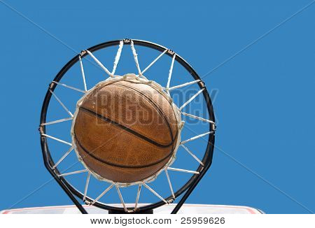 Basketball in the net against clear blue skies - concept of a successful endeavor