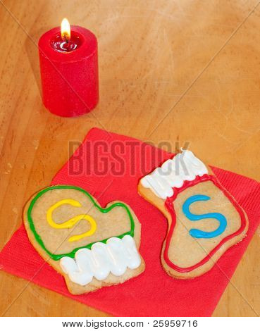 Santa's colorful cookies on red napkin on a wooden table with a candle