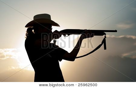 Silhouette of a young man in a cowboy hat shooting with a shotgun