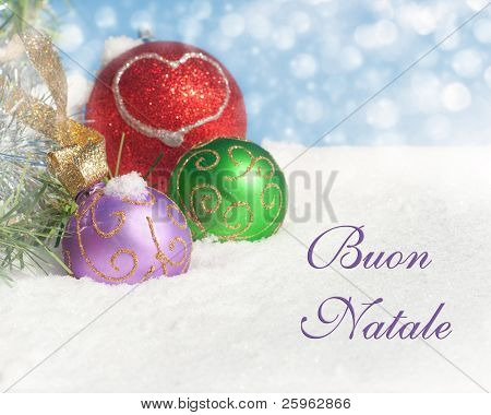 Colorful Christmas ornaments in snow with text Buon Natale, Merry Christmas in Italian
