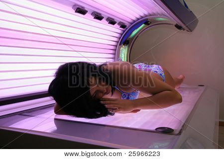 Dark-hair girl tanning in solarium.