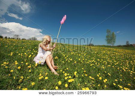 Beautiful blond girl with long hair in dandelion field