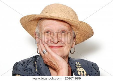 Portrait of the old woman in a hat on a light background