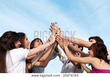 Gruppe junger Männer, die Hände, um eine Flasche mit Wasser Strecken