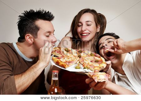 The cheerful company of youth eating a pizza
