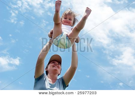 Happy mother playing with a small daughter against the sky
